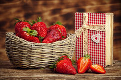 Strawberries. Beautiful strawberries with cookbook on wooden table royalty free stock photo
