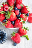 Strawberries, berries and raspberries on rustic wooden table Royalty Free Stock Image