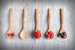 Strawberries, berries and raspberries on rustic wooden table Royalty Free Stock Photos