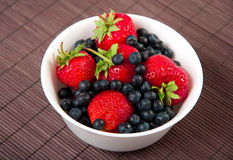 Strawberries, bilberry on bamboo tablecloth Stock Images
