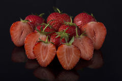 Strawberries on black acrylic Royalty Free Stock Photos