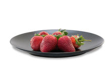 Strawberries on black ceramic plate isolated Royalty Free Stock Image