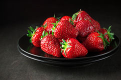 Strawberries in black plate Stock Photos
