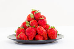 Strawberries on the black plate on white background. Photo of strawberries on the black plate on white background Royalty Free Stock Image