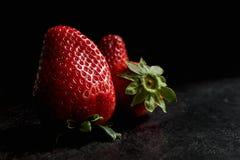 Strawberries on black textured background, dark food stock photo