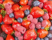 Strawberries, blackberries, and rasperries mixed soft fruits. Mix of berries like strawberries, raspberries and blackberries on plate for fruit background Royalty Free Stock Image
