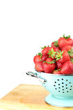 Strawberries in a blue colander. On white background Stock Image