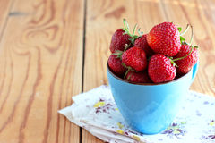 Strawberries in a blue cup Stock Images