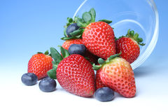 Strawberries and blueberries. A bunch of ripe, plump strawberries and blueberries spilling out of a glass bowl Stock Image