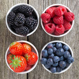 Strawberries, blueberries, blackberries and raspberries in bowls. Top view, close-up Royalty Free Stock Images