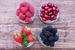 Strawberries, blueberries, blackberries and. Raspberries in bowls, top view, close-up Stock Image