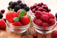 Strawberries, blueberries, blackberries and. Raspberries in bowls, top view, close-up Royalty Free Stock Photos