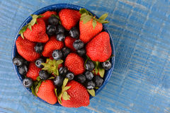 Strawberries and Blueberries in Blue Enamelware Bowl. High angle shot of strawberries and blueberries in a blue enamelware bowl. The bowl is on a rustic wooden Royalty Free Stock Images