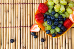Strawberries, blueberries and grapes on a bamboo mat Royalty Free Stock Photo