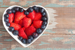 Strawberries and blueberries in a heart shaped bowl. Royalty Free Stock Image