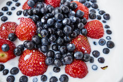 Strawberries, blueberries and milk in a white bowl Royalty Free Stock Images