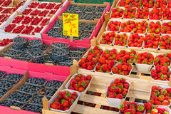 Strawberries, blueberries and raspberries for sale. At a market Stock Photos