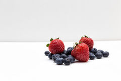 Strawberries and Blueberries. Three Strawberries and a bunch of blueberries Royalty Free Stock Images