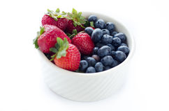 Strawberries and blueberries in white bowl. Fresh strawberries and blueberries in white bowl and isolated white background Stock Images
