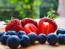 Strawberries and blueberries on wooden bowl. stock photo