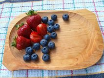 Strawberries and blueberries in wooden bowl on kitchen towel. Stock Image