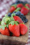 Strawberries and Blueberries in Wooden Dish. Strawberries and blueberries in a long wooden serving dish on top of a checkered tablecloth Stock Photos