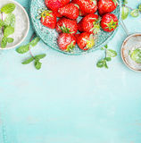 Strawberries  border with mint and sugar on  turquoise shabby chic background, top view Royalty Free Stock Images