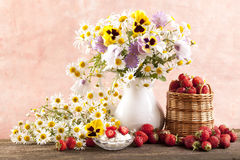 Strawberries and bouquet of  flowers Stock Images