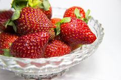 Strawberries in a Bowl. Fresh strawberries with leaves resting in a glass bowl with a grey/white background Stock Photos
