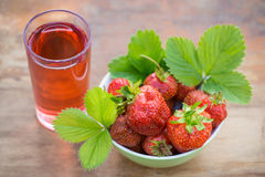 Strawberries in a bowl and a glass of strawberry juice on a wooden table Stock Photos
