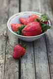 Strawberries in a bowl on gray wooden background Stock Images