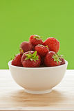 Strawberries in bowl before green background Stock Image