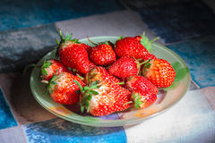 Strawberries in bowl on table Stock Photos