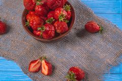 Ripe red strawberry top view on a blue table. Strawberries in a bowl top view on a blue wooden surface royalty free stock photography