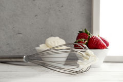 Strawberries in bowl with whipped cream and wire whisk Stock Images