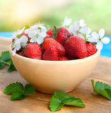 Strawberries in a bowl on wood table Stock Images
