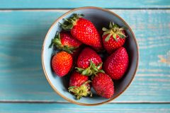 Strawberries in a bowl on a wooden background. Healthy eating. stock photos