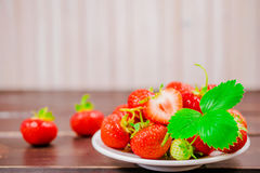 Strawberries in bowl on wooden table with low key and copy spacen Royalty Free Stock Photos
