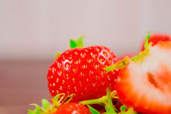 Strawberries in bowl on wooden table with low key and copy spacen Royalty Free Stock Image