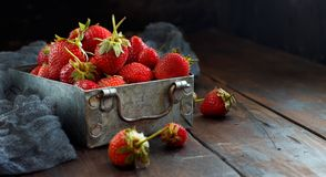 Strawberries in a box on a  table. Strawberries in a box  on a dark wooden table Royalty Free Stock Photos