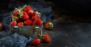 Strawberries in a box on a  table. Strawberries in a box  on a dark wooden table Royalty Free Stock Photography
