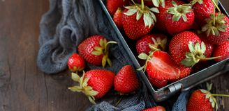 Strawberries in a box on a  table. Strawberries in a box  on an old wooden table Royalty Free Stock Photos