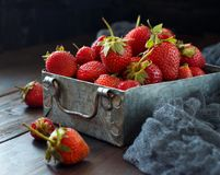 Strawberries in a box on a  table. Strawberries in a box  on a dark wooden table Royalty Free Stock Photo