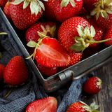 Strawberries in a box on a  table. Strawberries in a box  on a white wooden table Royalty Free Stock Photography