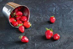 Strawberries in a bucket of ice on the concrete background backg. Ripe red strawberries in a metal bucket of ice on a small concrete background Stock Photos