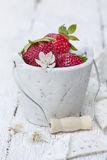 Strawberries in a bucket. On a white wooden background Royalty Free Stock Images