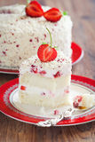 Strawberries cake. Sponge cake slice with whipped cream, strawberries, white chocolate and dried rose petals, selective focus Stock Photos