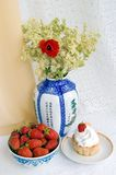 Strawberries, cake and a vase with flowers Stock Photos
