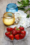 Strawberries, candles and white peony flower. On wooden table. Summer party decor. Selective focus Stock Photo