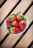Strawberries in ceramic bowl. Strawberries in white ceramic bowl on wooden table Stock Images